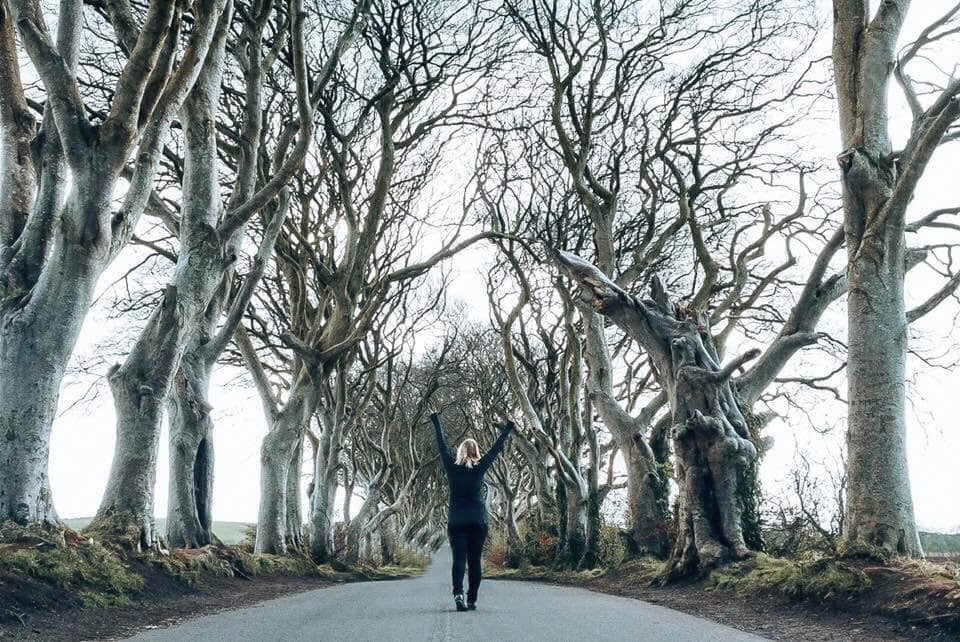 Woman standing in middle of Dark Hedges raising hands in peace signs