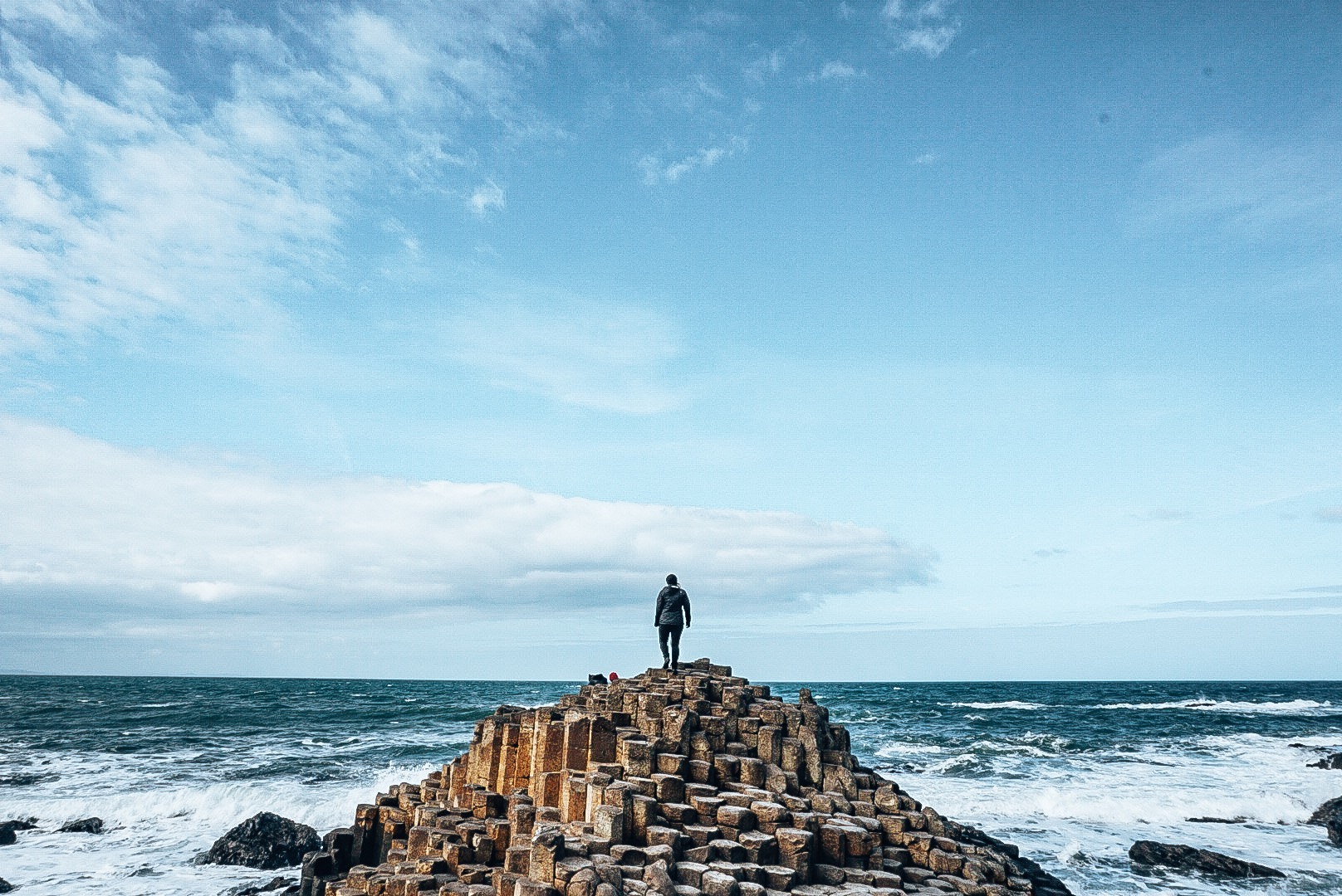 Woman standing on small mountain of hexagonal rocks jutting out from the ocean