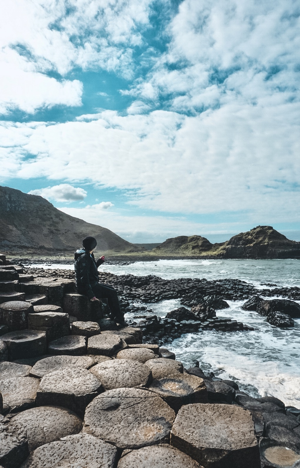 Sitting on the hexagonal rocks at Giant's Causeway in Northern Ireland