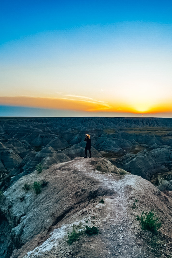 Woman standing near Badlands at sunrise, playing with hair