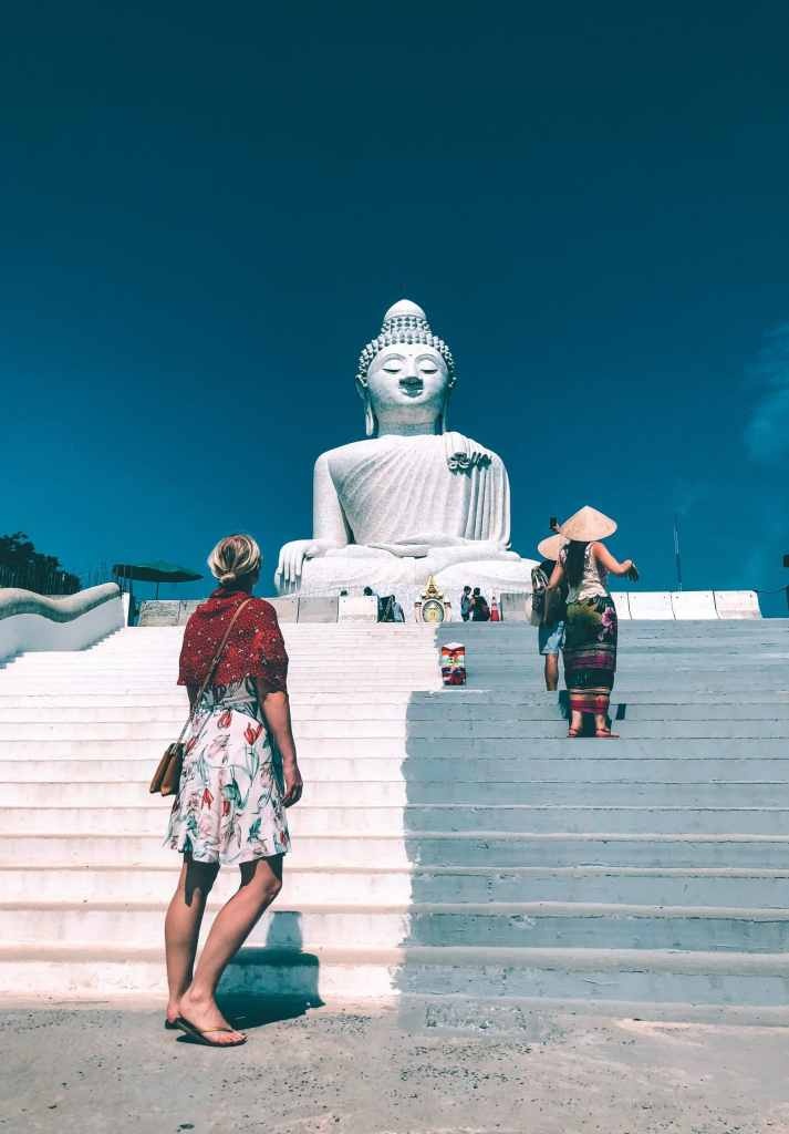 Woman standing at the base of Big Buddha, watching as other women walk up stairs