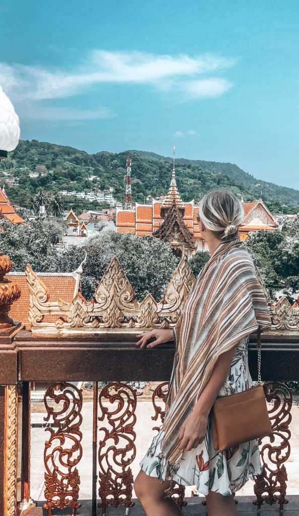 Woman wearing a scarf around her shoulders looking out to the Buddhist temple