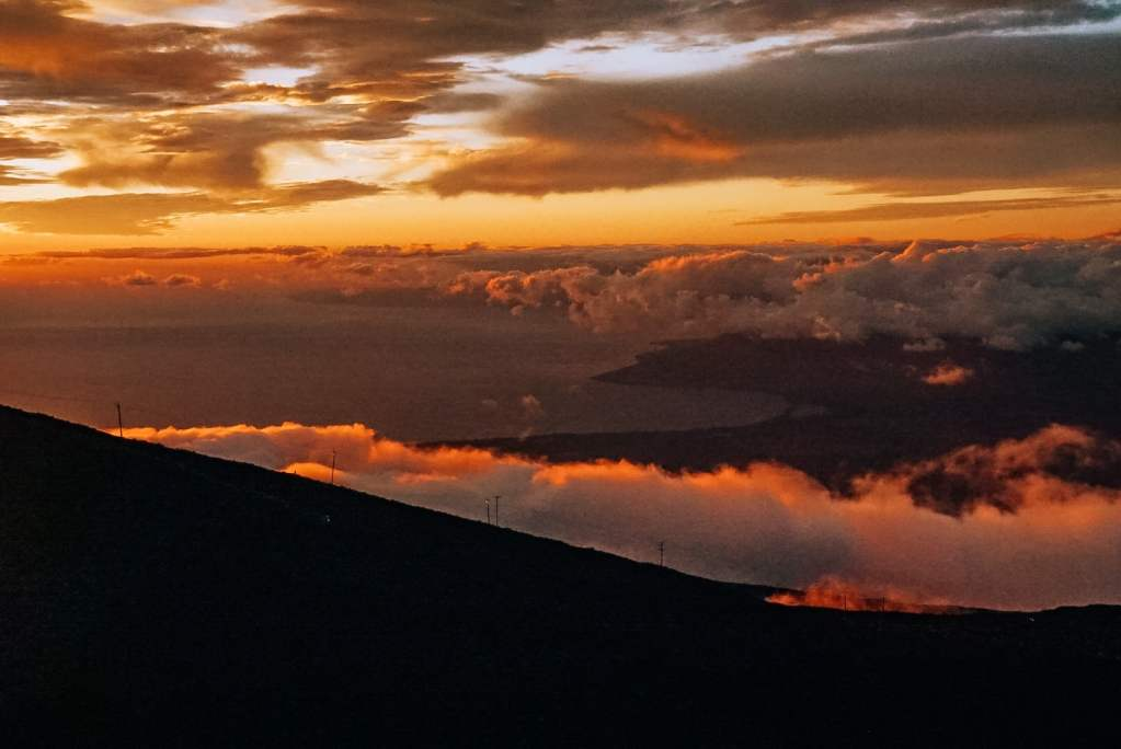 Haleakala sun setting and the clouds have moved so you can see the coast