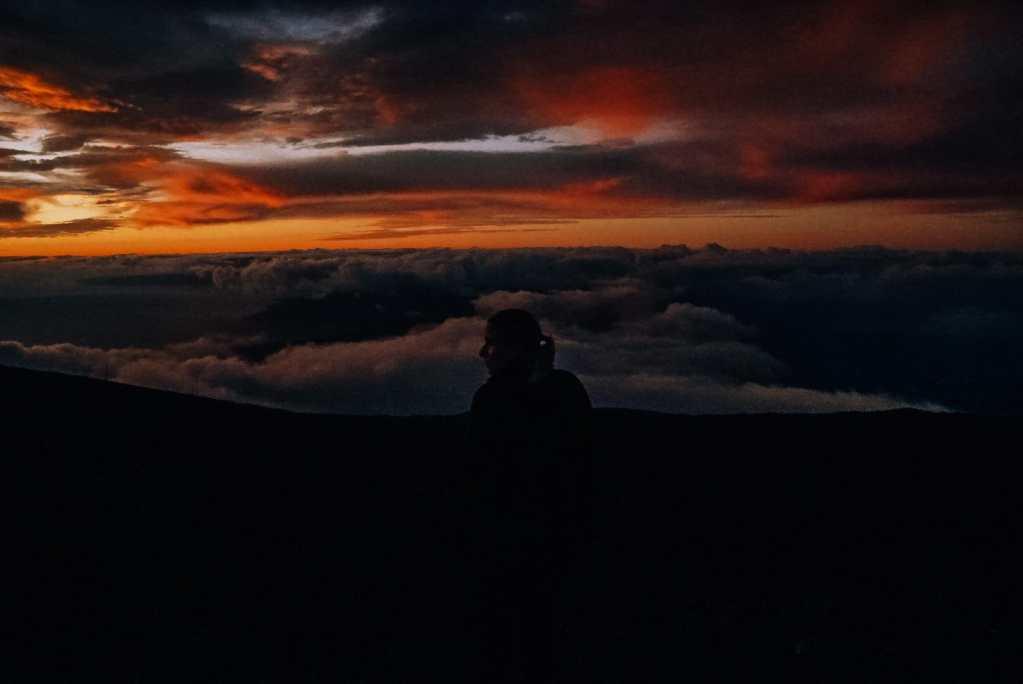 Woman sitting on the edge as the sun goes down at Haleakala