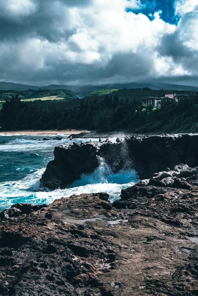 Water crashing up over coastline with jutting rocks shaped like dragon's teeth