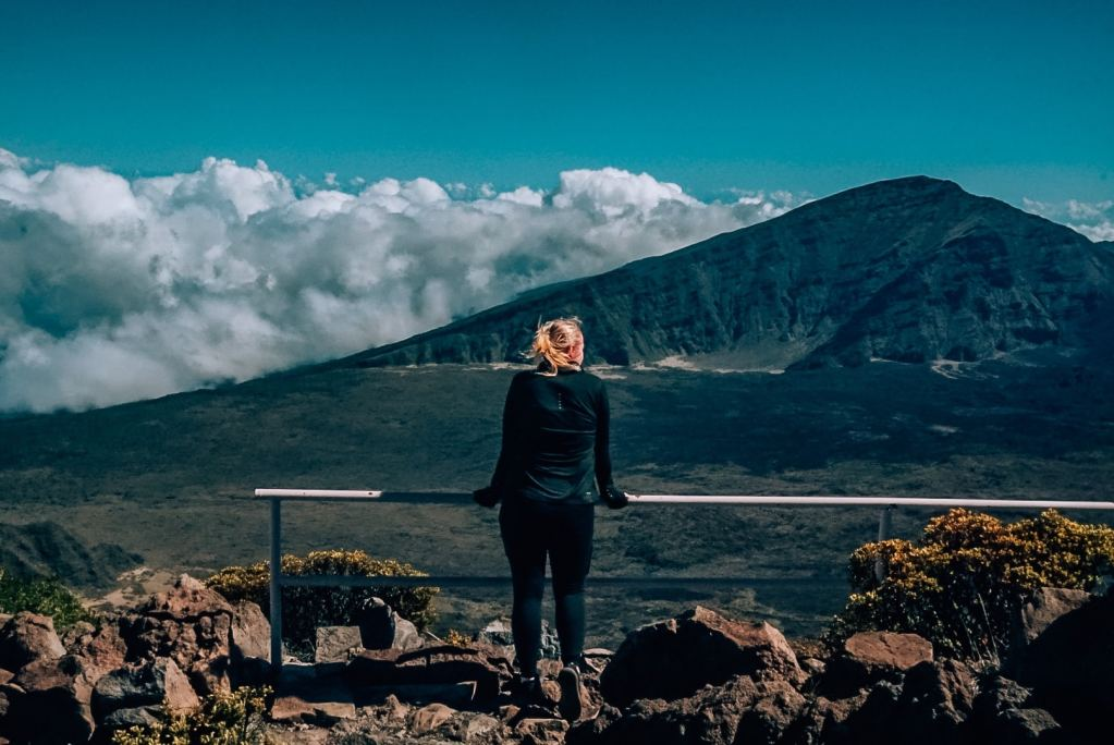 Woman standing in front of a railing in front of the crater at Haleakala