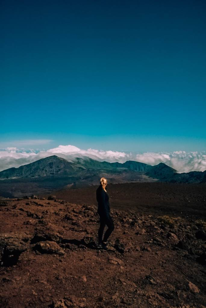 Woman standing atop the Sliding Sands trailhead to start hiking into the Haleakala crater