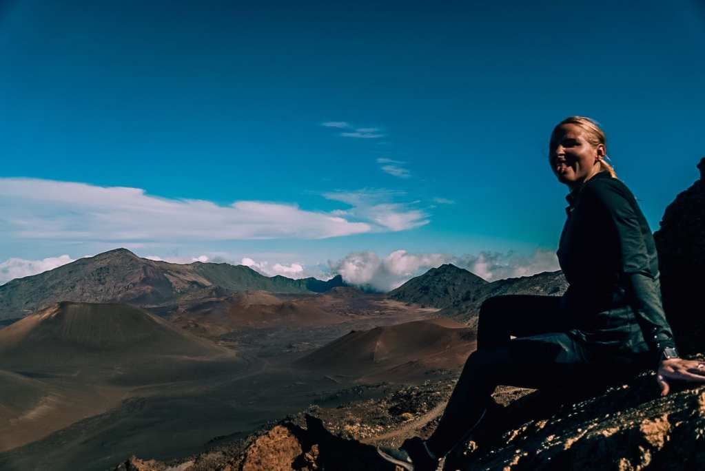 Woman sitting on a rock smiling with her tongue out in front of the Haleakala crater
