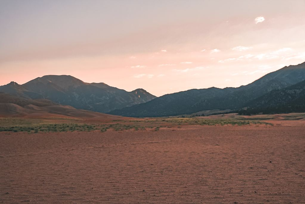 View of the Great Sand Dunes from the base of the dunes facing the mountains during sunrise with the sky pastel purple, pink, and yellow
