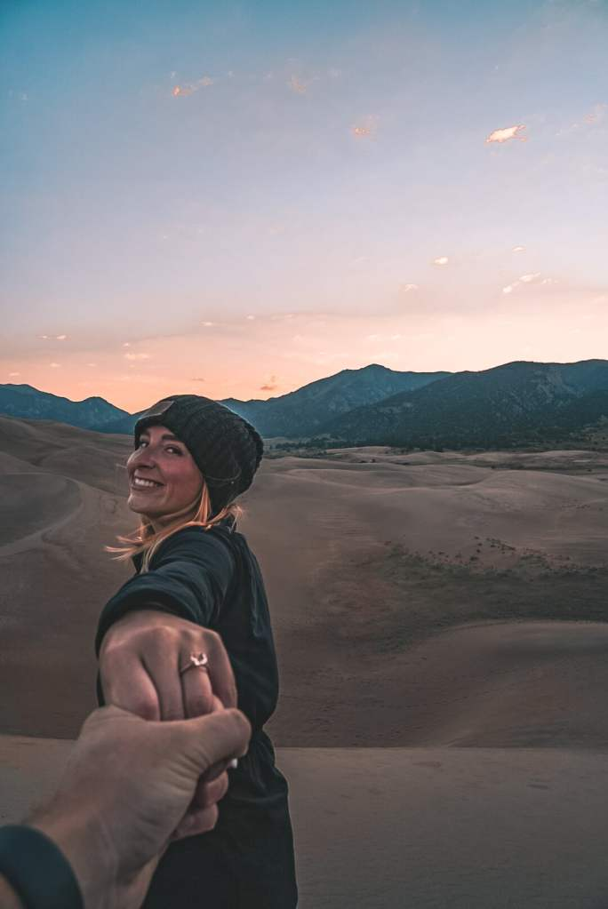 Man holding woman's hand with engagement ring, woman is looking back at camera smiling, both are standing in front of the mountains at the Great Sand Dunes