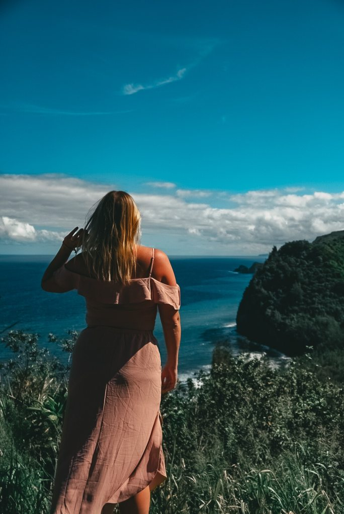 Woman standing with her back to the camera and her left hand up in her hair looking out at Polulu Valley