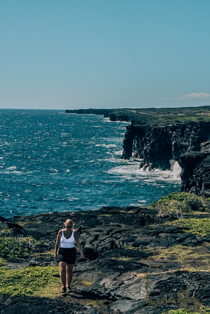 Woman walking along the coast toward the camera with the coast and the famous Volcanoes National Park sea arch