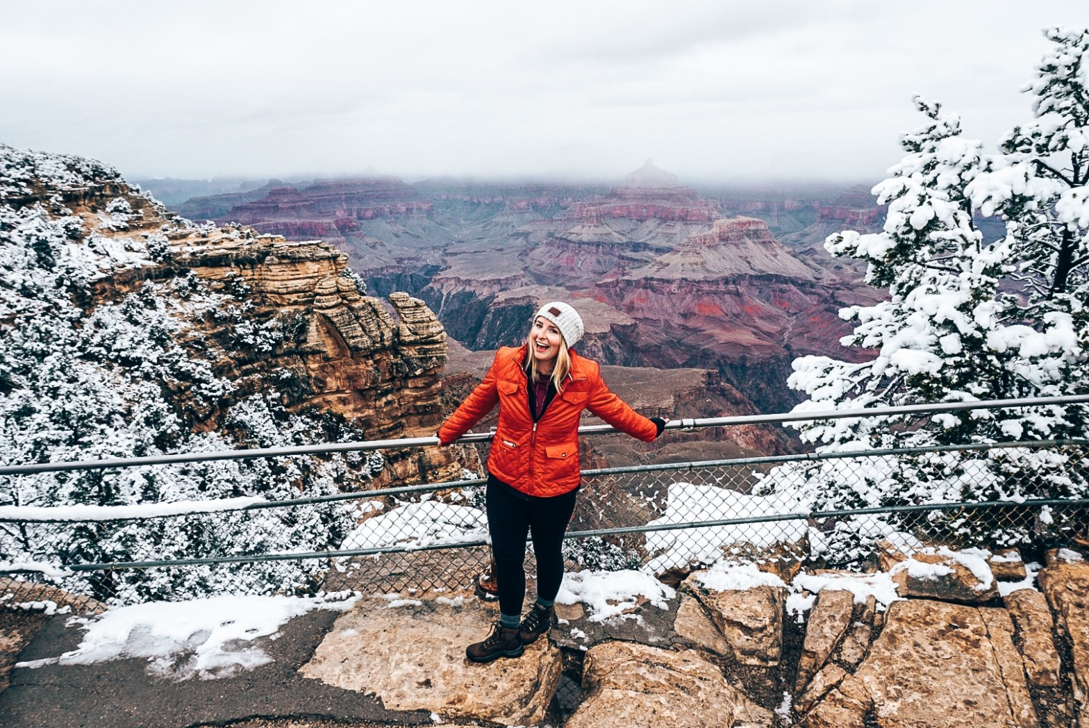 Woman standing along the fenceline at the Grand Canyon during the winter, with the trees and rocked covered in snow