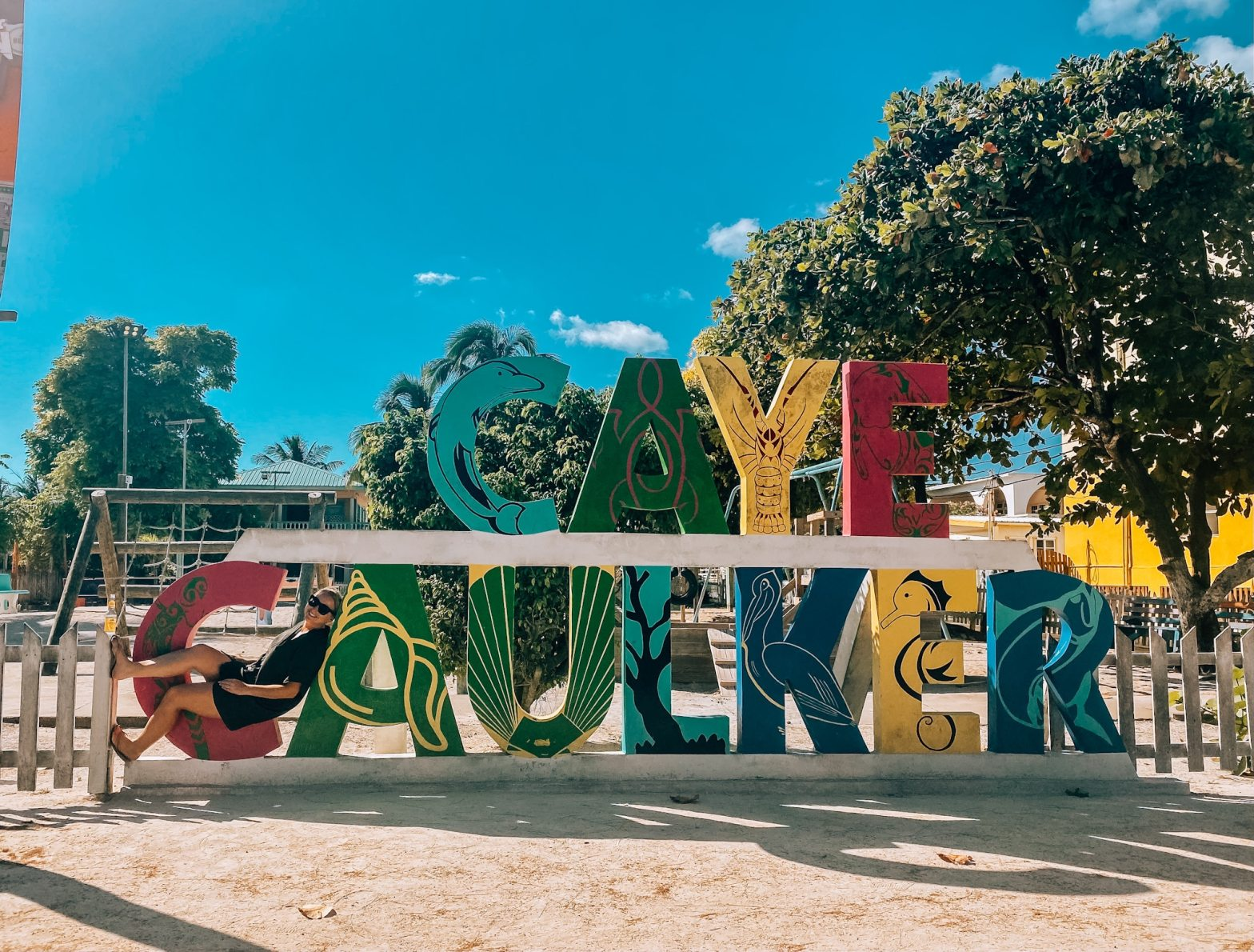 Woman sitting in the C of the Caye Caulker sign