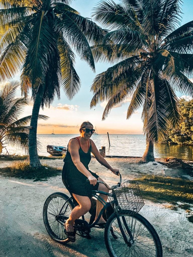 Woman biking at sunset next to palm trees