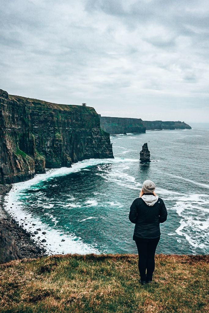 Woman standing on the edge of the Cliffs of Moher