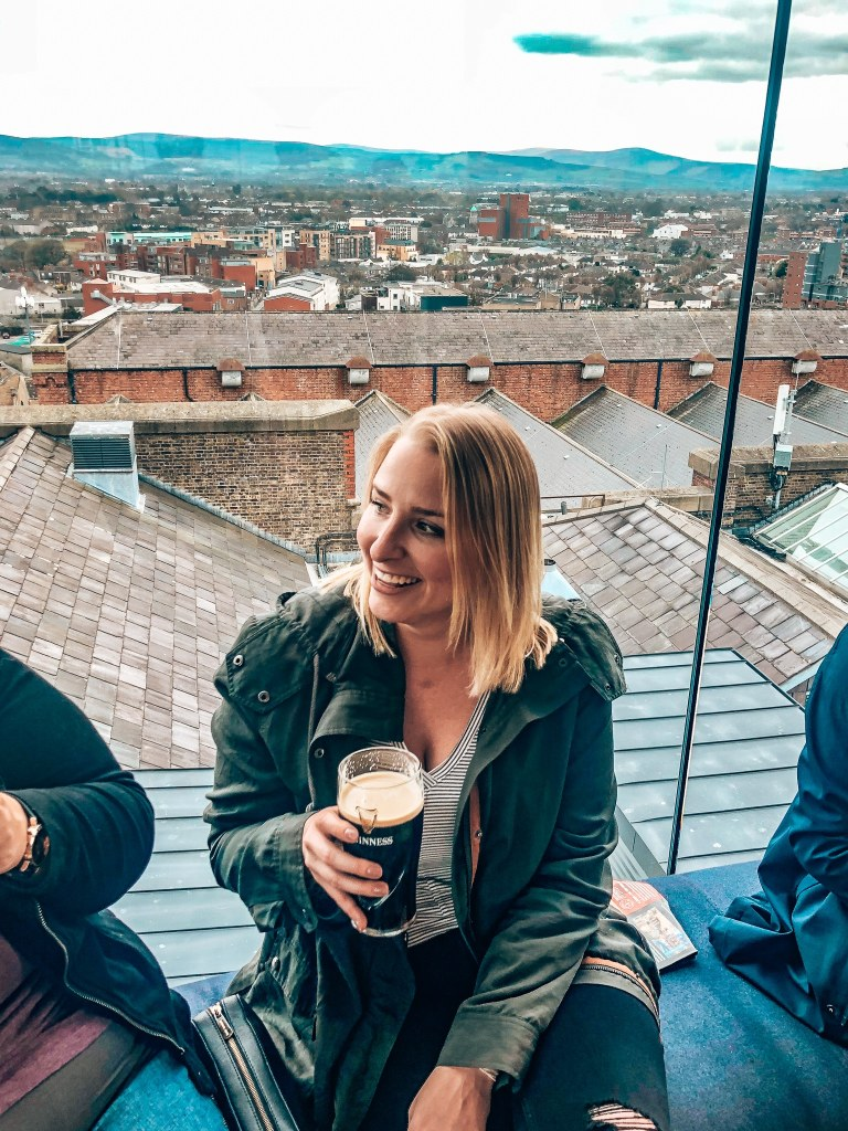 Woman holding a Guinness while at the Gravity Bar in Dublin, with a view of the city behind