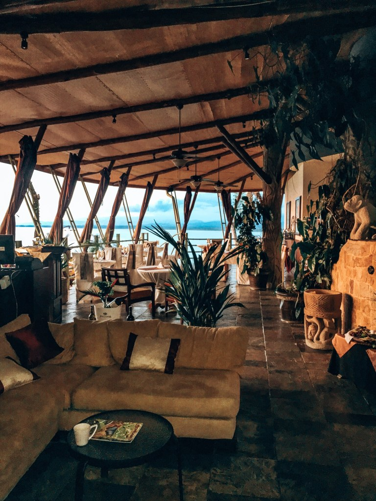 View of the lobby and dining area of the Issimo Suites hotel - a couch to hang out in the lobby and then covered outdoor seating with amazing views of the ocean