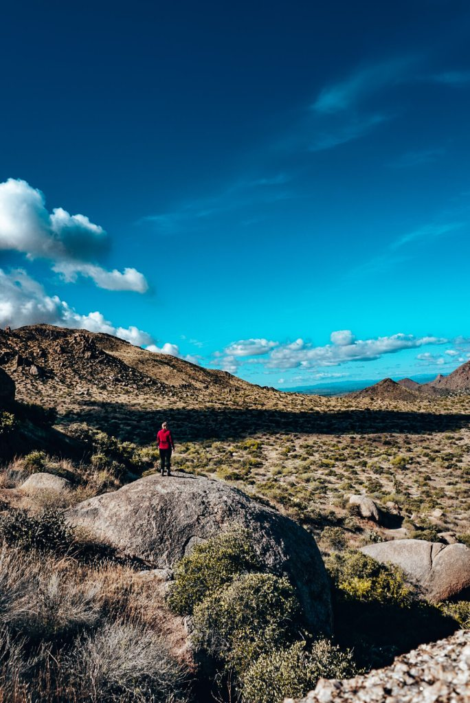 Woman standing on a giant rock along Tom's Thumb hiking trail