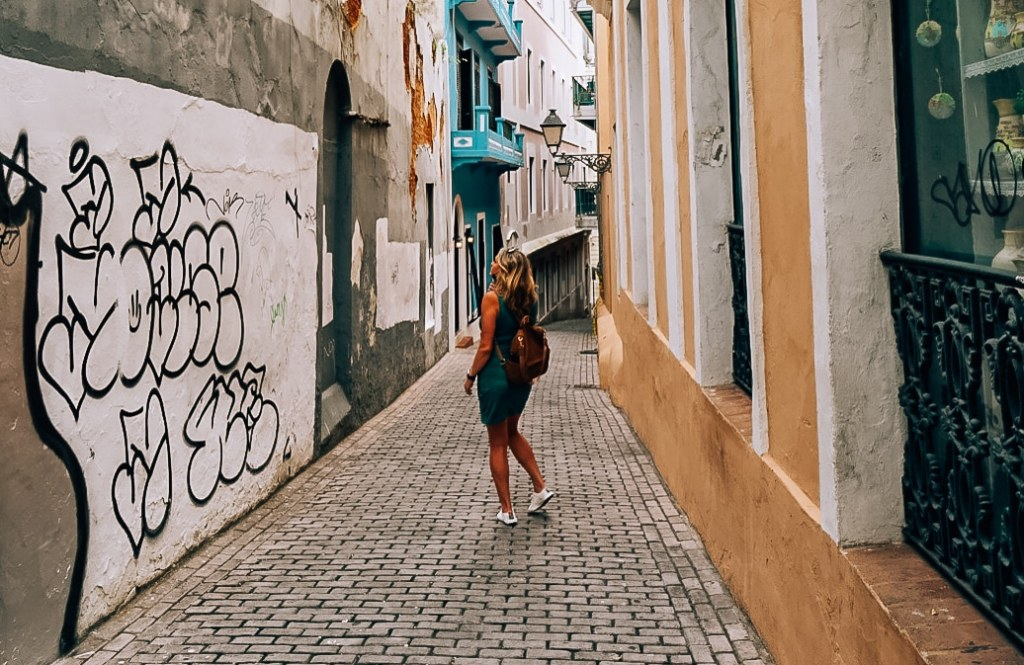 Woman wearing dress with tennis shoes and backpack standing in the middle of alley in Old San Juan, Puerto Rico