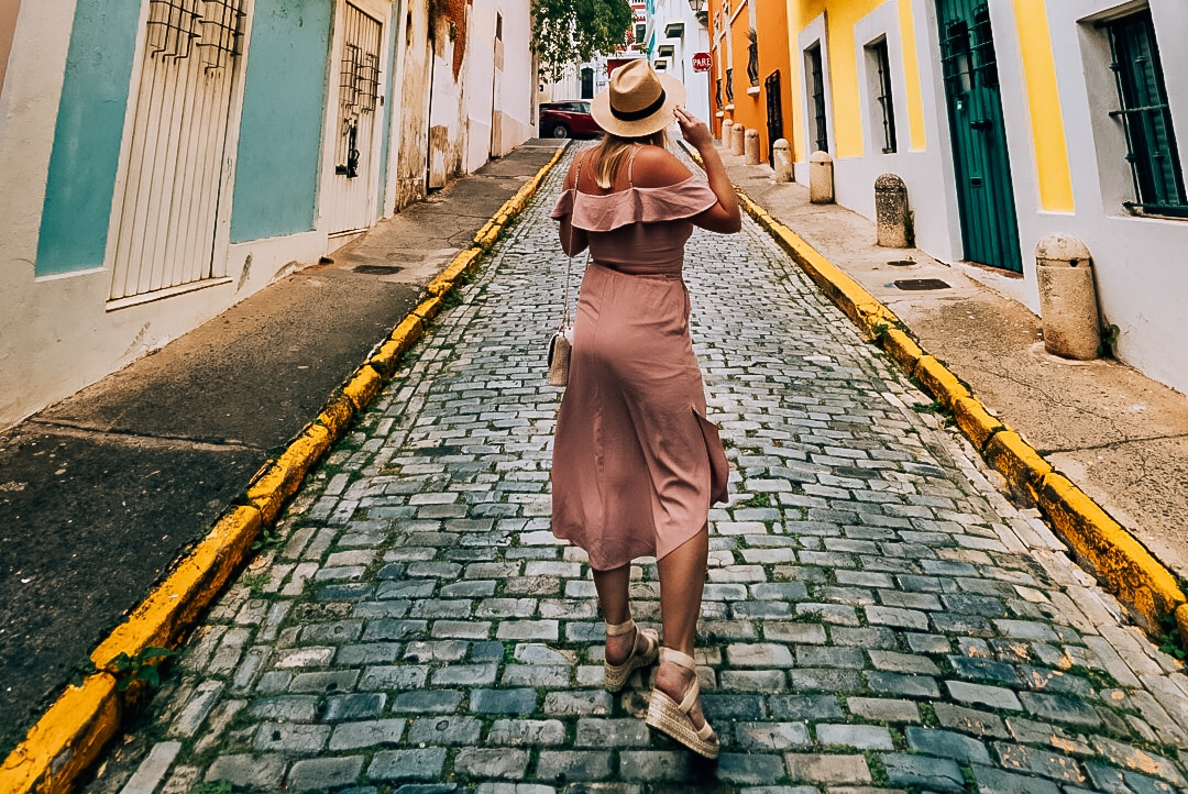 Woman standing on brick road in Old San Juan holding her hat