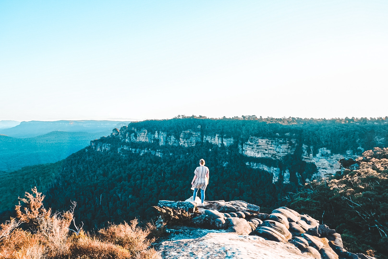 Woman standing above Blue Mountains and looking into the valley below