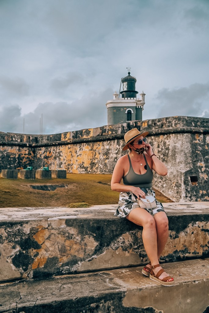 Woman sitting on one of the ledges of El Morro in Old San Juan