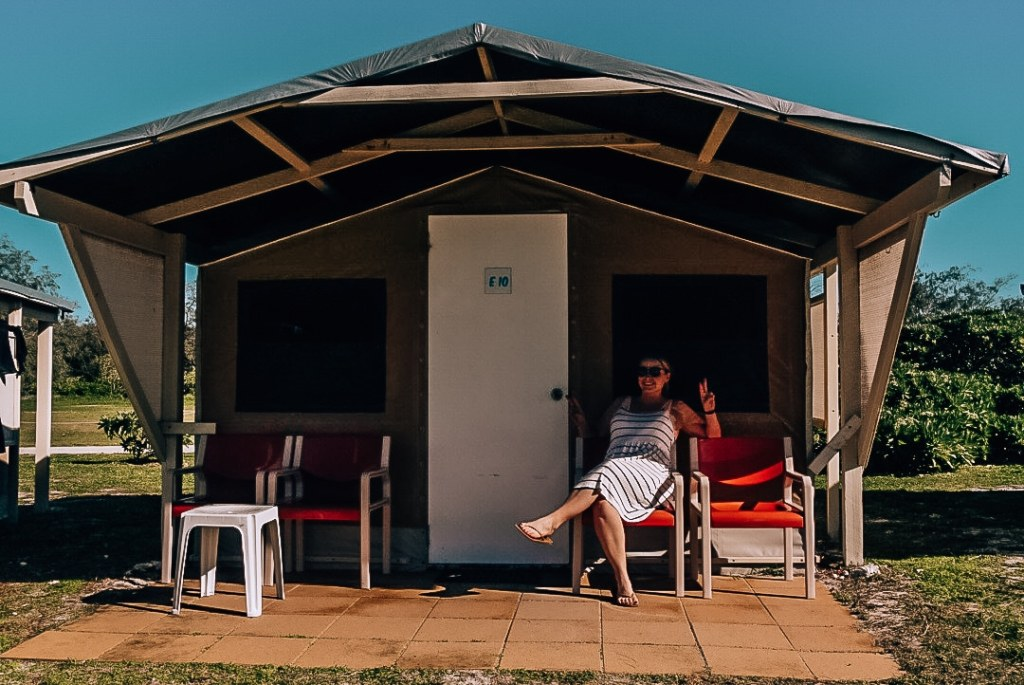 Woman sitting in a chair holding up peace signs in front of her hut at the Lady Elliot Island Eco Resort