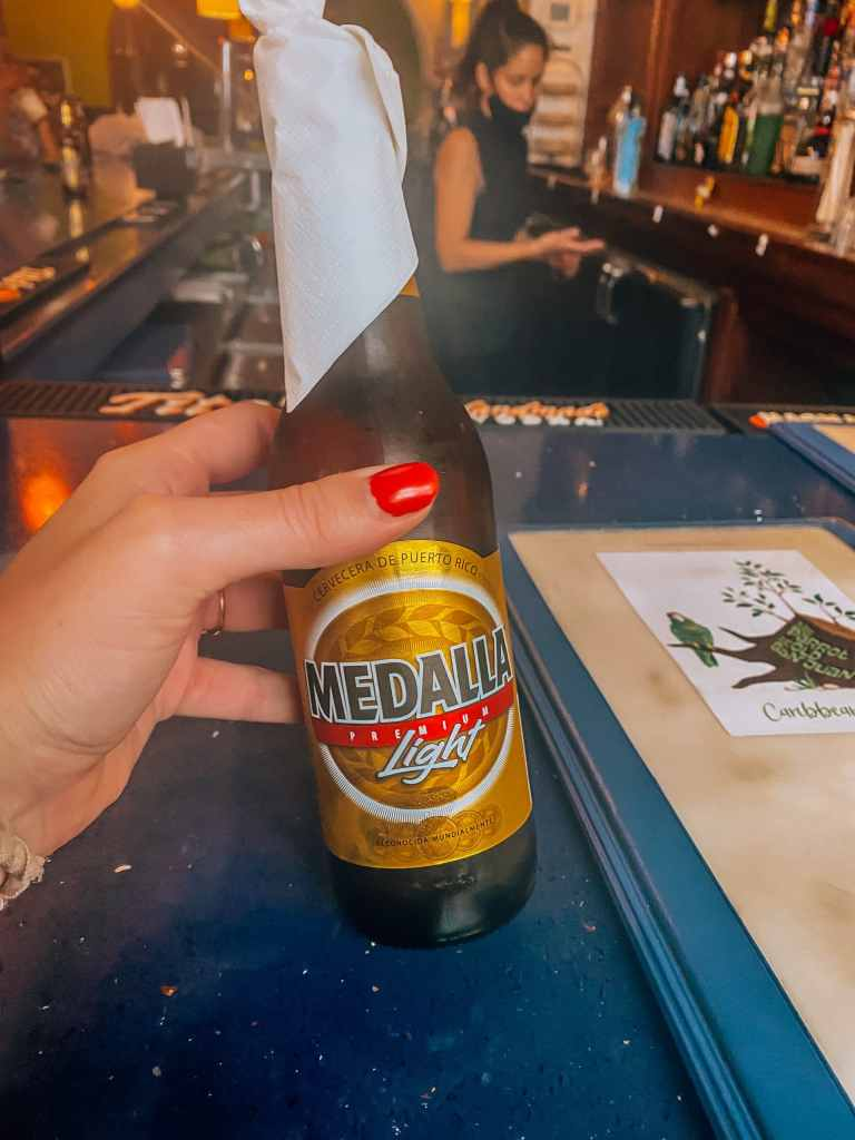 Woman holding a bottle of Medalla beer