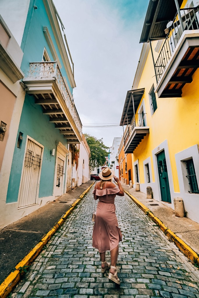 Woman standing in between two colorful buildings in Old San Juan