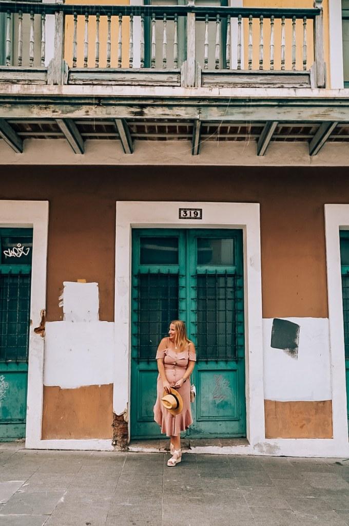 Woman standing in front of teal door