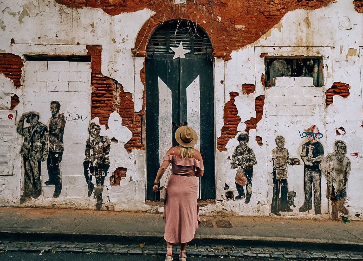 Woman standing in front of the Puerto Rican flag monument in Old San Juan