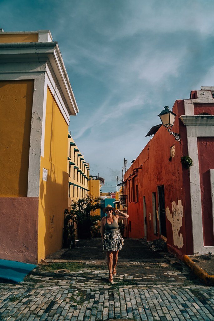 Woman standing in between two colorful buildings