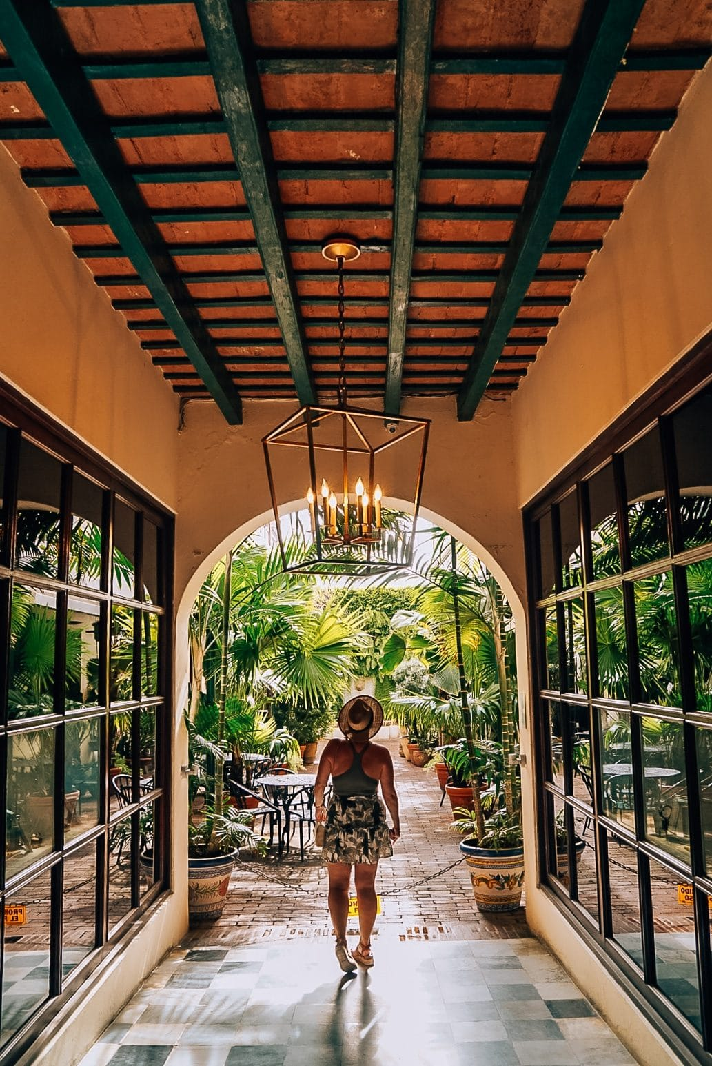 Woman standing under chandelier and in front of lots of greenery