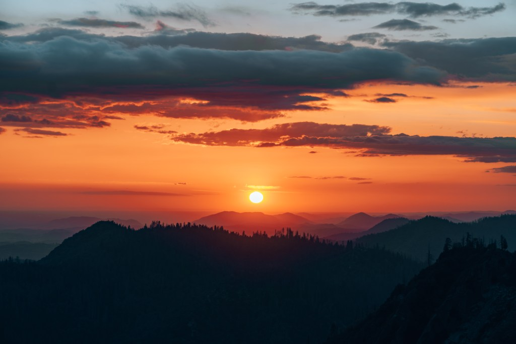 Sun setting behind the mountains and trees atop Moro Rock in Sequoia National Park