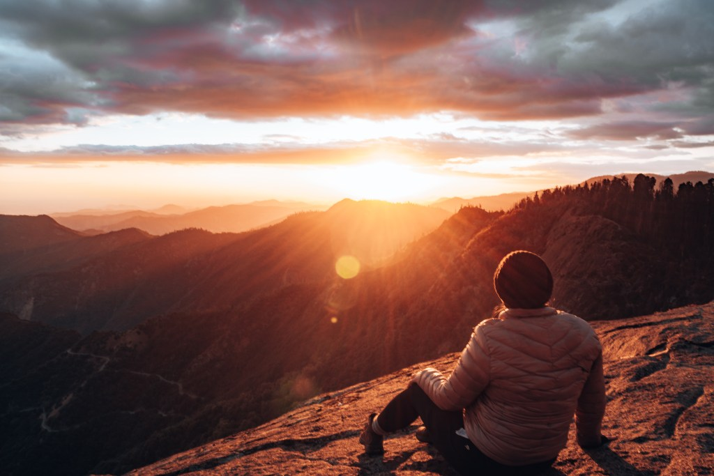 Woman sitting atop Moro Rock looking out at the sunset over the mountains at Sequoia National Park