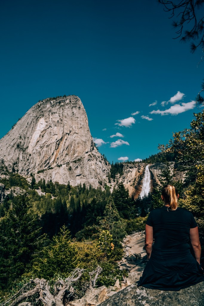 Woman sitting on a rock with Nevada Falls in the background