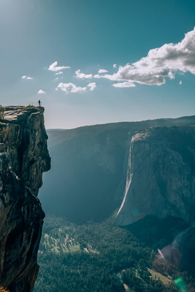 Woman standing far away at the top of Taft Point with Yosemite Valley in the background