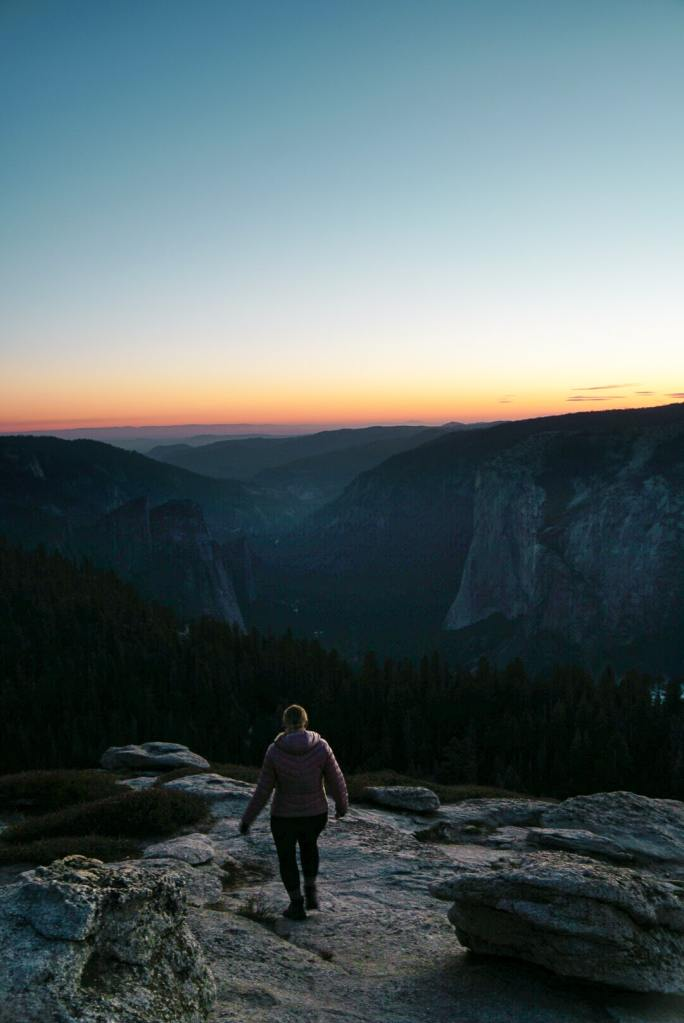 Woman in a jacket walking down the rocks on Sentinel Dome toward the sunset in the distance