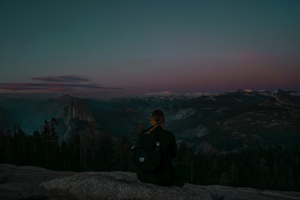Woman sitting on the rock looking out at the sunset sky over the mountains at Yosemite