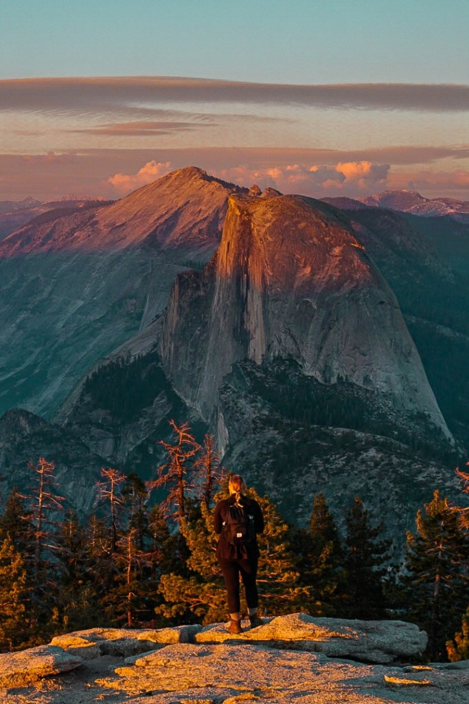 Woman standing atop Sentinel Dome looking out at Half Dome over sunset