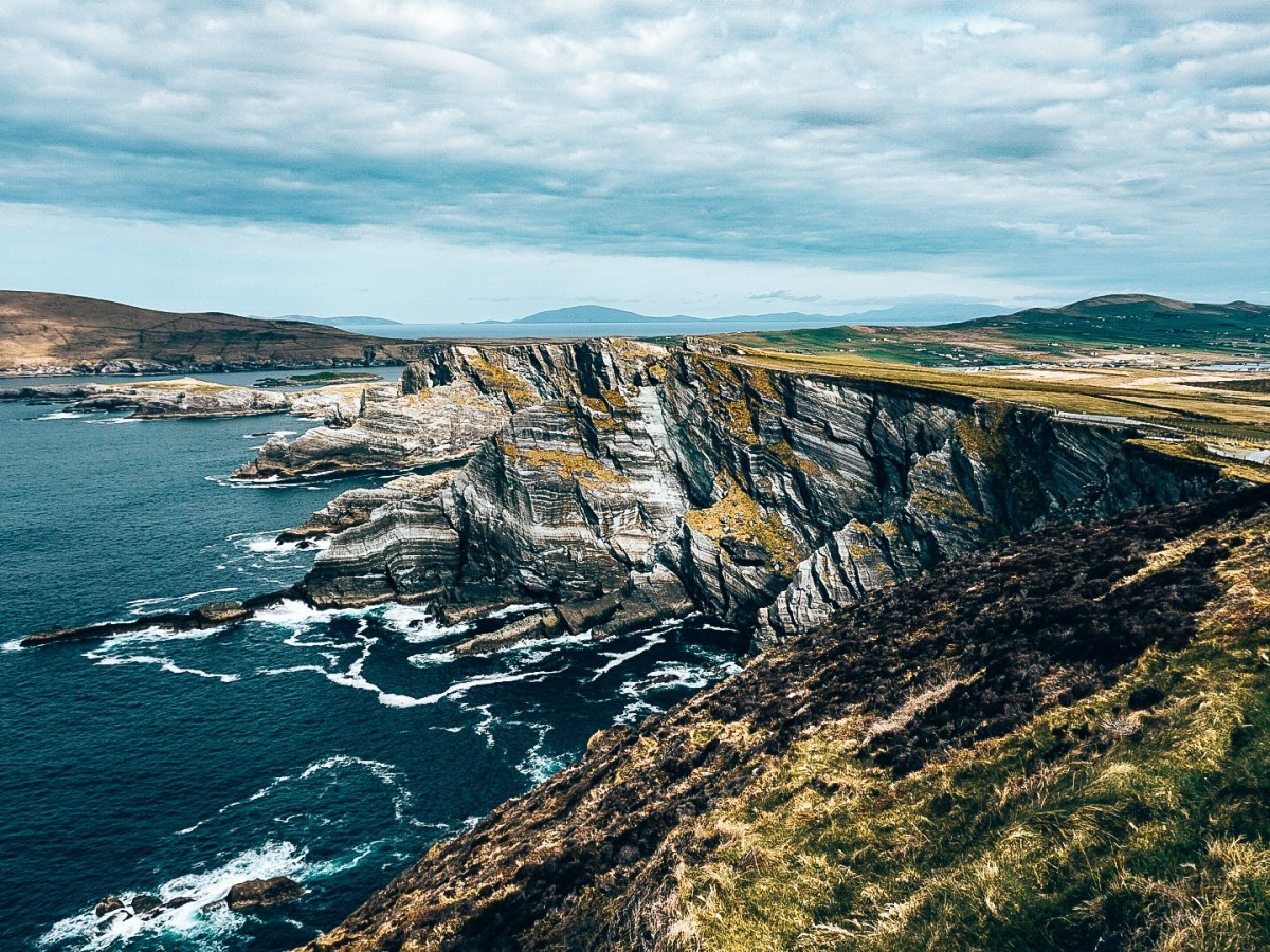 View of the Kerry Cliffs in Kerry County, Ireland. Water is splashing up against the jagged & striated cliffs.