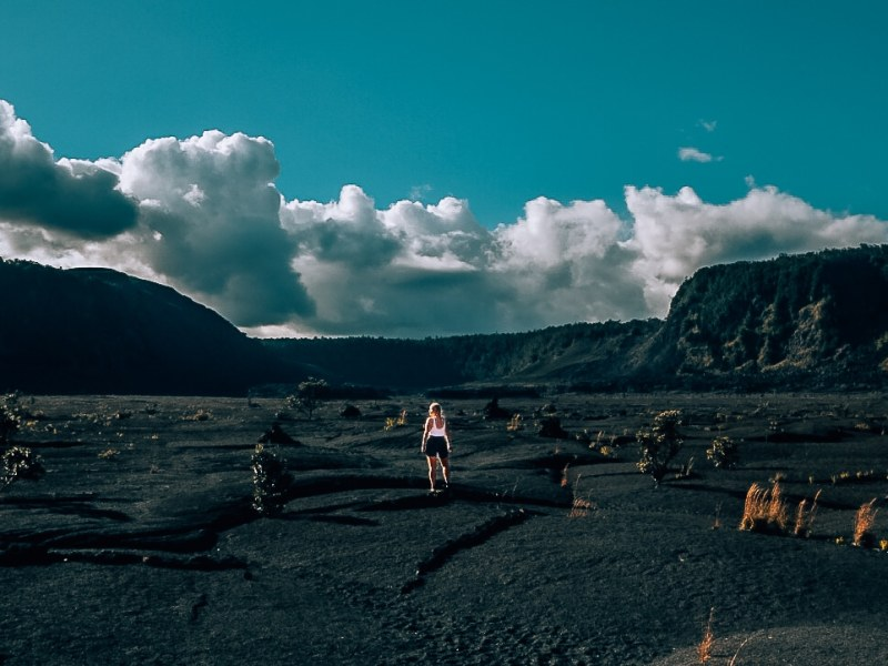 Woman standing in the middle of the dried lava bed of the Kilauea Iki Trail in Volcanoes National Park of Hawaii.