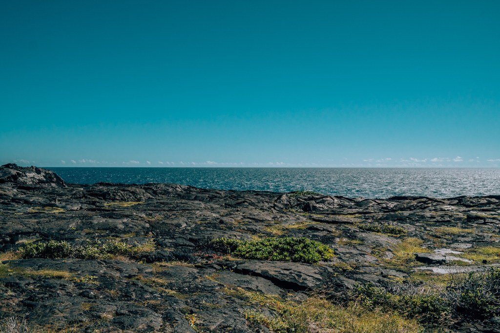 View of the solidified lava bed in the foreground with the ocean horizon in the background