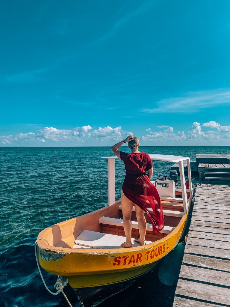 Woman standing in a red swimsuit cover in a boat looking out to the ocean