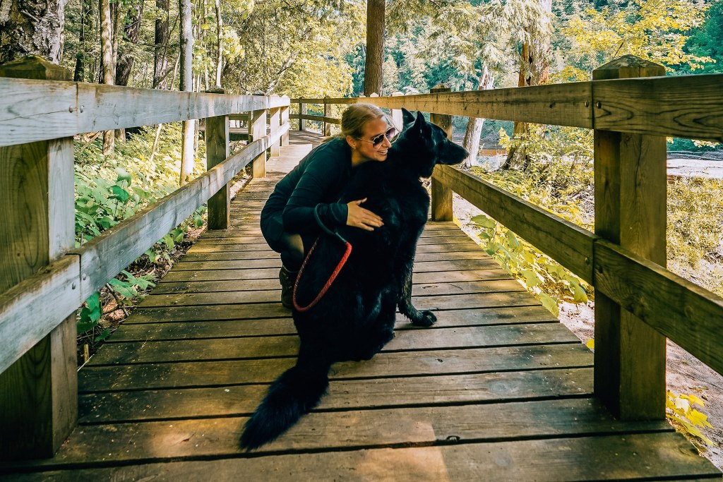 Woman bent over on a wooden walkway hugging her all black German Shepherd in the Porcupine Mountains