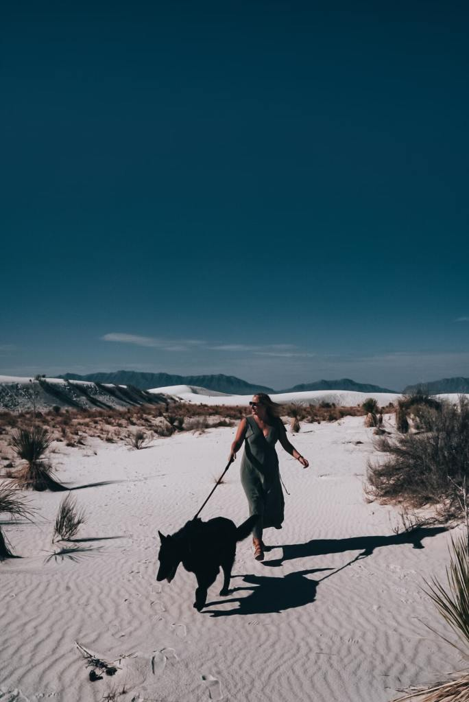 Woman in green dress walking large all black German Shepherd through White Sands National Park