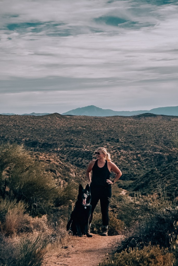 Woman and her large, all black German Shepherd standing on a hiking trail in Arizona