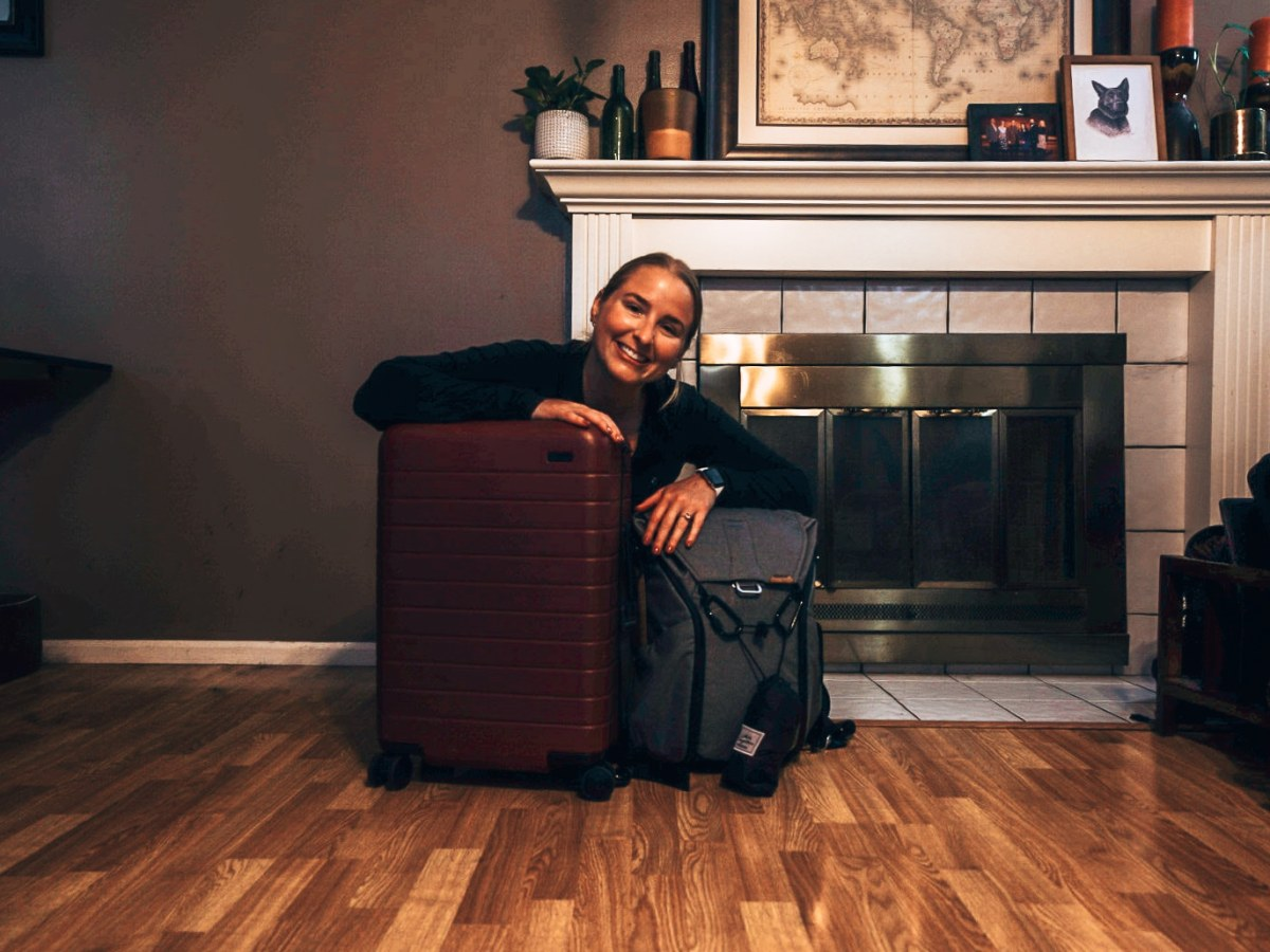 Woman sitting with a small carry-on roller luggage and a backpack