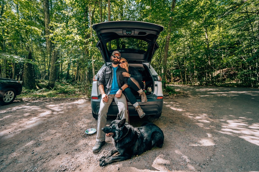 Man and woman sat in the back of a Jeep Cherokee with their black German Shepherd laying down in front during a road trip